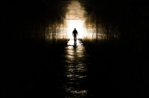 Man walking toward a cross formed by light reflecting off the grungy walls of an underground culvert.
